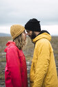 Young couple rubbing affectionately noses, Lapland, Norway - KKAF02299