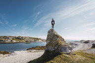 Finland, Lapland, man standing on top of a rock at the coast - KKAF02314
