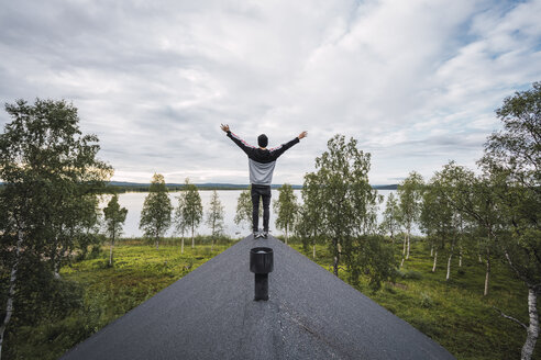 Finland, Lapland, man standing on roof of a house at a lake with raised arms - KKAF02317