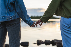 Finland, Lapland, close-up of two young women hand in hand at the lakeside at twilight - KKAF02323