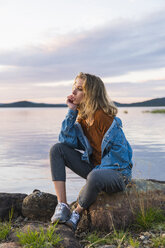 Finland, Lapland, young woman sitting on a rock at the lakeside - KKAF02326