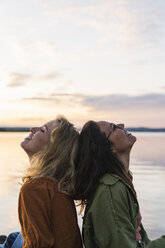 Finland, Lapland, two happy young women back to back at the lakeside at twilight - KKAF02329