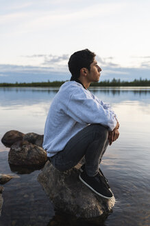 Finland, Lapland, man sitting on a rock in a lake - KKAF02338