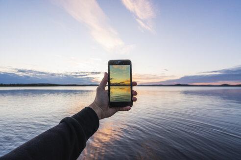 Finland, Lapland, man taking cell phone picture of stunning lake at twilight - KKAF02341