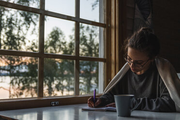 Finland, Lapland, young woman sitting at the window at a lake writing into diary - KKAF02344