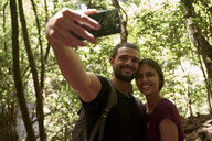 Spain, Canary Islands, La Palma, smiling couple taking a selfie in a forest - PACF00151