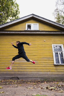 Dynamic athlete jumping in front of a yellow wood house - KKAF02353