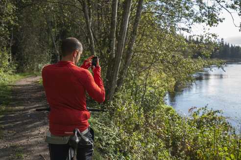 Mountain biker standing at lake taking pictures with his smartphone - KKAF02359