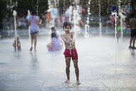 Carefree boy playing with water from a fountain - AZOF00069