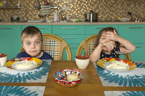 Funny portrait of boy and his little sister eating breakfast in the kitchen - VGF00002