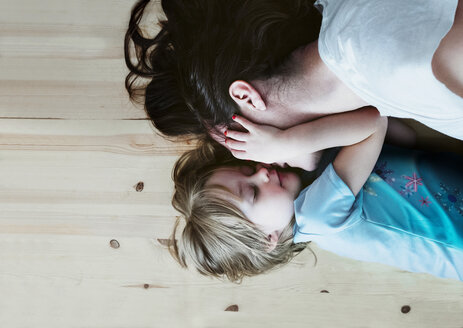 Daughter caressing mother, lying on floor - PSIF00109