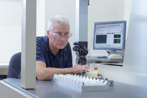 Engineer inspecting sizes of Polytetrafluoroethylene (PTFE) parts in engineering factory - CUF43856