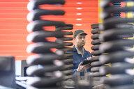 Engineer inspecting springs in train engineering factory - CUF43877