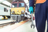 Close up of engineer holding spanner with locomotive in train engineering factory - CUF43880