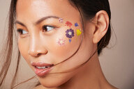 Woman with floral face paint on cheek - CUF43916