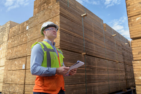 Worker with stacks of timber in storage at port - CUF43988