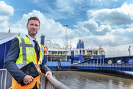 Businessman with loading ferry ships in port in background - CUF44000