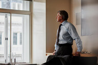 Businessman in office looking out of window pensively - CUF44009