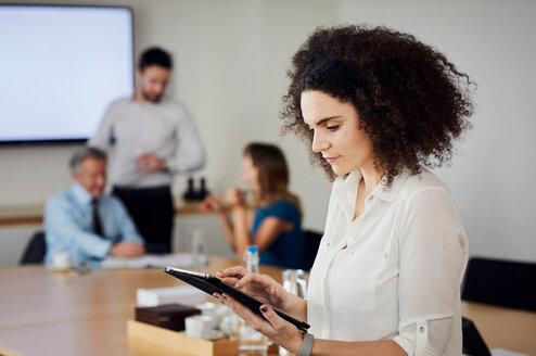 Businesswoman in office using digital tablet - CUF44015
