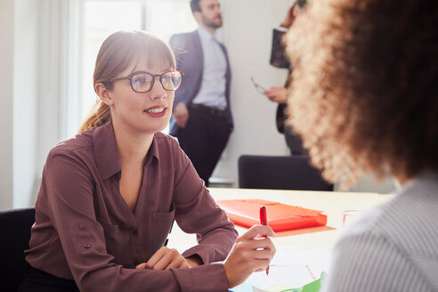Businesswoman in office talking to colleague - CUF44030