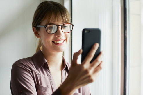 Woman looking at smartphone smiling - CUF44036