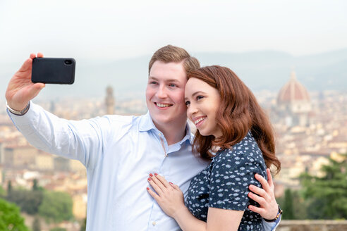 Young couple taking selfie, Santa Maria del Fiore in background, Florence, Toscana, Italy - CUF44087