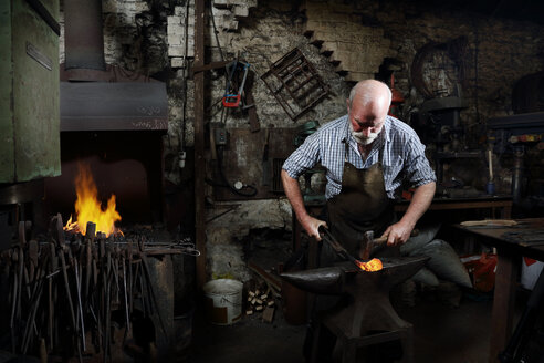 Blacksmith hammering red hot metal in blacksmiths shop - CUF44132
