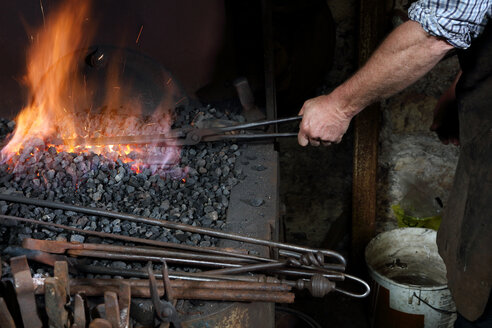 Blacksmith heating metal in forge fire in blacksmiths shop, cropped - CUF44135