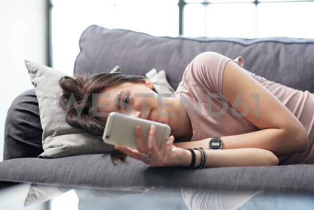 Teenage girl lying on sofa looking at smartphone - CUF44141 - T2 Images/Westend61