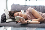 Teenage girl lying on sofa looking at smartphone - CUF44141
