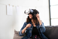 Teenage girl on sofa looking through virtual reality headset - CUF44144