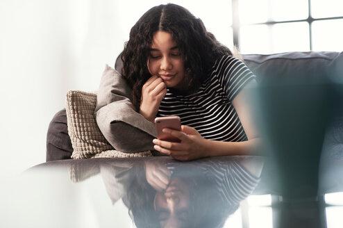 Teenage girl sitting on sofa looking at smartphone - CUF44150