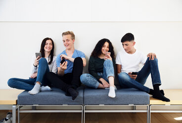 Four high school students on seating looking at smartphones - CUF44159