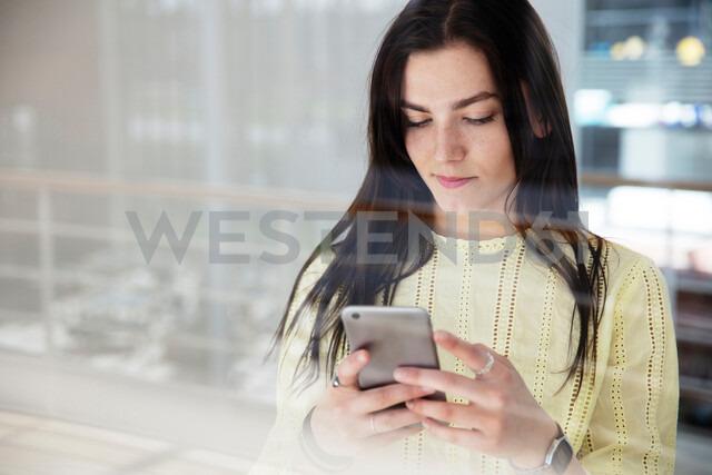 High school girl in school lobby looking at smartphone - CUF44162