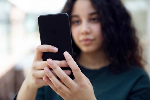High school girl in school corridor looking at smartphone - CUF44165