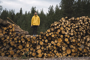 Man with camera standing on stack of wood - KKAF02379