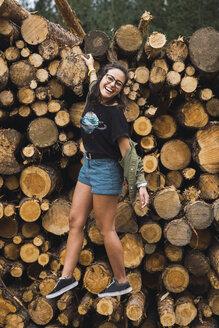 Happy young woman balancing on stack of wood - KKAF02382