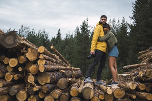 Young woman embracing man with camera on stack of wood - KKAF02385