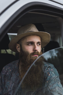Bearded young man looking out of car window - KKAF02388