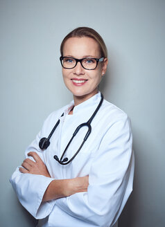 Portrait of smiling female doctor with stethoscope wearing glasses - PNEF01002
