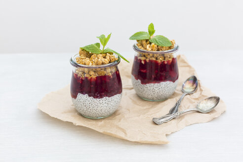 Two glasses of chia pudding with coconut milk, red fruit jelly and peanut granola topping - JUNF01359