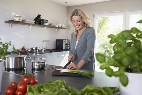 Smiling woman cutting spring onions in kitchen - PDF01723