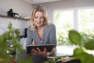 Smiling woman using tablet in kitchen - PDF01732