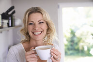 Portrait of smiling woman drinking coffee in kitchen - PDF01738