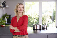 Confident woman wearing red blouse standing in kitchen - PDF01741