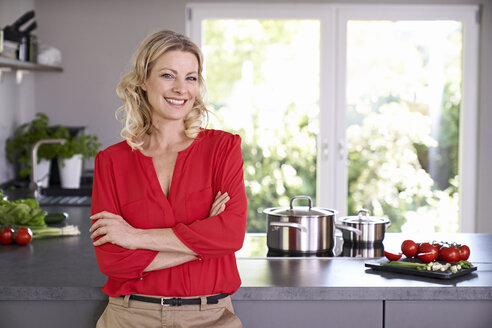 Portrait of smiling woman wearing red blouse standing in kitchen - PDF01744