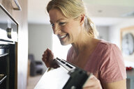 Smiling woman cooking in kitchen looking into oven - PDF01753