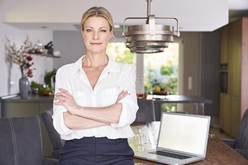 Portrait of confident businesswoman at home with laptop on table - PDF01759