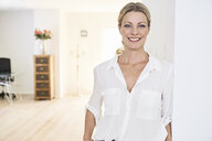 Portrait of smiling woman wearing white blouse at home - PDF01762