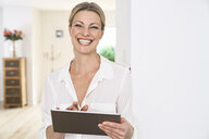 Portrait of happy woman using tablet at home - PDF01765